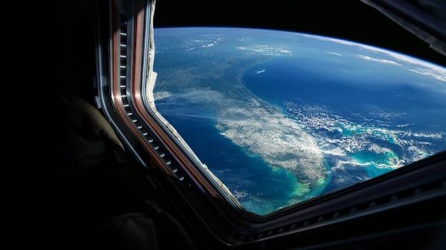 우주선은 창에서 볼 수 있는 놀라운 푸른 행성 지구 근처로 날아갑니다. 공간, 개념에서 여행과 관광객. 구름이 형성되는 지구의 아름다운 우주 전망. 우주에 있는 호텔