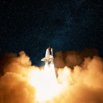 Spaceship takes off with blast and puffs of smoke into the starry sky. rocket lift off and fly into space.