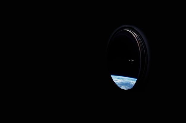 푸른 행성 지구와 iss 스테이션이 내려다보이는 우주선 창문. 우주 여행 개념입니다. 디자인 및 텍스트를 위한 장소