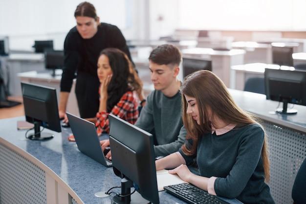 Просторная территория. группа молодых людей в повседневной одежде, работающих в современном офисе