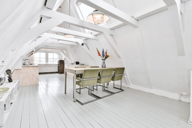 Просторная мансардная комната квартиры с обеденным столом и стульями возле открытой кухни под крышей с балками