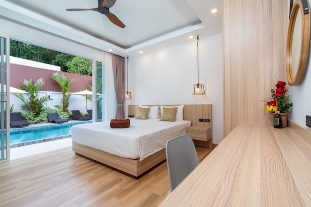Spacious bedroom pool access with sliding door overlooking to garden with sun bed and umbrella