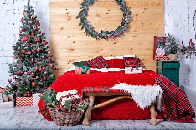 Просторная спальня с украшенной елкой и рождественским венком на стене
