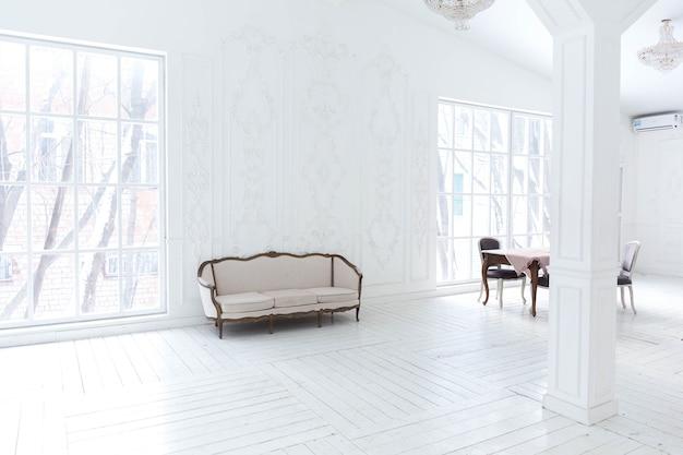 Просторная светлая гостиная со стильным классическим дизайном с антикварным декором и красивой шикарной мебелью в старинном стиле.