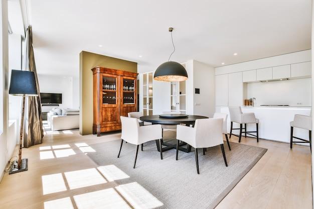 Просторная столовая со столом и стульями в современной квартире в стиле минимализм.