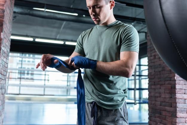 Spacious gym. good-looking strong fighter wearing khaki shirt training hard in light spacious gym