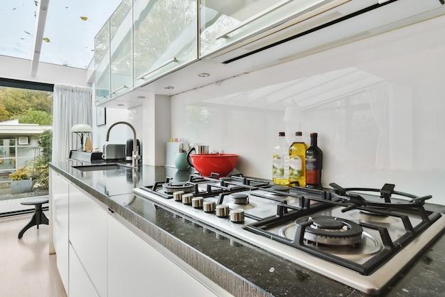 Просторная кухня с белыми и матовыми шкафчиками и встроенной хромированной техникой при дневном свете.