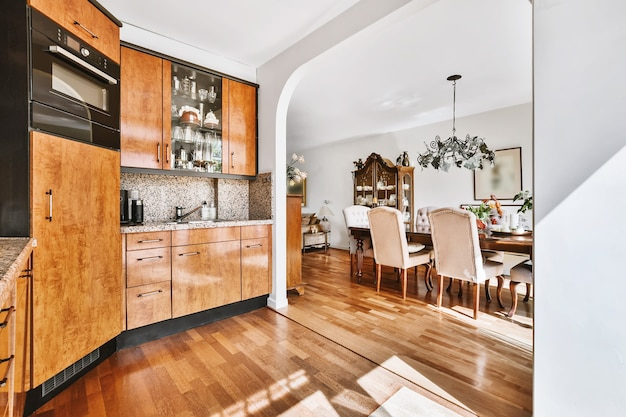 明るい日光の下で木製のキャビネットと黒い要素と木製の寄木細工の床の広々としたキッチンルーム
