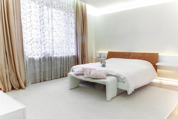 넓은 창문과 편안한 더블침대가 있는 넓은 조명 침실