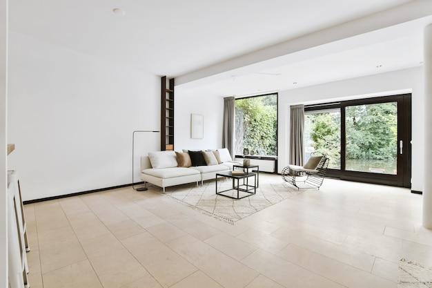 미니멀 한 스타일의 현대적인 아파트에 소파와 부드러운 쿠션이있는 넓은 거실