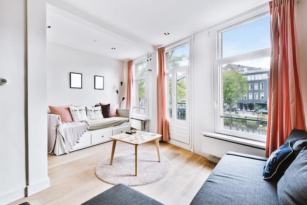 Просторная гостиная с диванами и мягкими подушками в современной квартире в стиле минимализм.