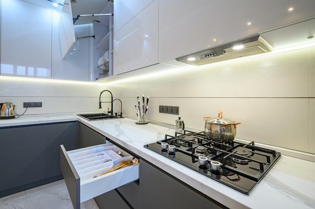 넓고 고급스러운 흰색과 어두운 회색의 현대적인 주방 인테리어, 일부 가구 서랍 및 문이 열려 있습니다.