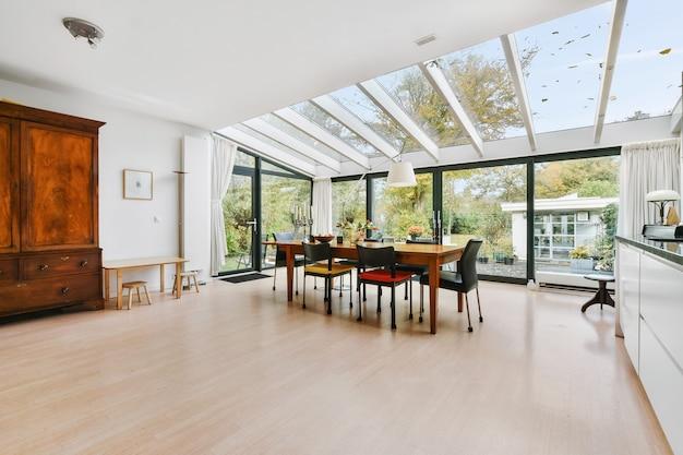 日光の下で木製のダイニングテーブルの上にガラスの壁と天井のある広々とした邸宅のキッチンルーム