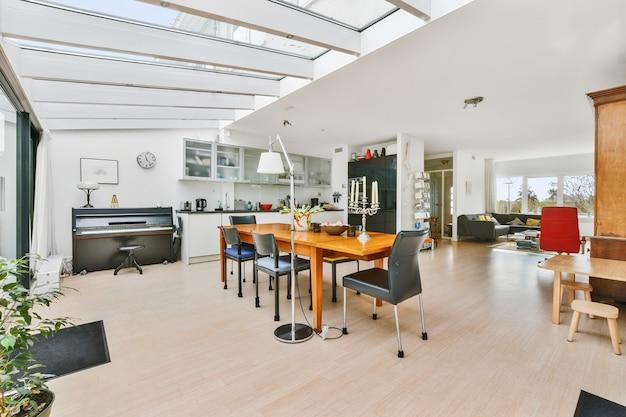 낮에 나무 식탁 위에 유리 벽과 천장이있는 넓은 맨션 주방 공간