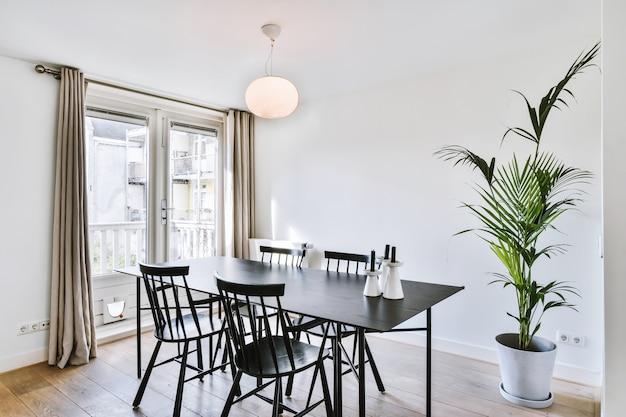 Просторная столовая в стиле минимализма со столом и стульями в современных апартаментах с белыми стенами и деревянным полом.