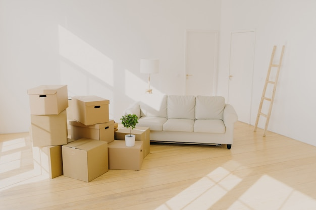 Spacious room with sofa, piles of cardboard boxes and ladder