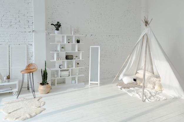 Просторные стильные современные модные апартаменты-лофт в бело-серых тонах, залитые солнечным светом. кирпичная стена и детский домик в форме вигвама.