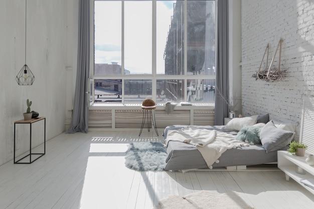 Просторные стильные современные модные апартаменты-лофт в бело-серых тонах, залитые солнечным светом. кирпичная стена, стеллажи, кровать из поддонов и детский домик-вигвам.