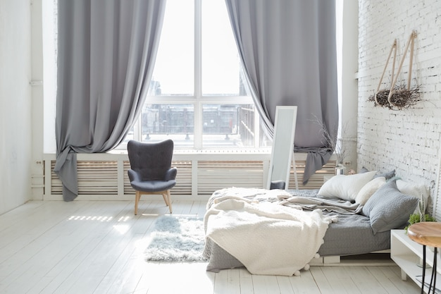 Просторные стильные современные модные апартаменты-лофт в бело-серых тонах, залитые солнечным светом. кирпичная стена, стеллаж, поддон