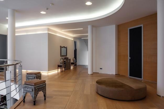 スタイリッシュな彫刻が施された家具を備えた豪華な家の広々とした2階の廊下