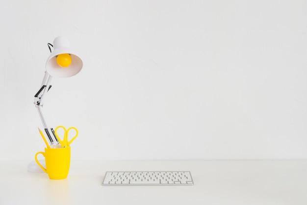 Просторное рабочее место с желтой кружкой и клавиатурой