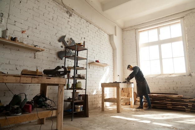 Spacious workshop interior with handyman working with power tools equipment