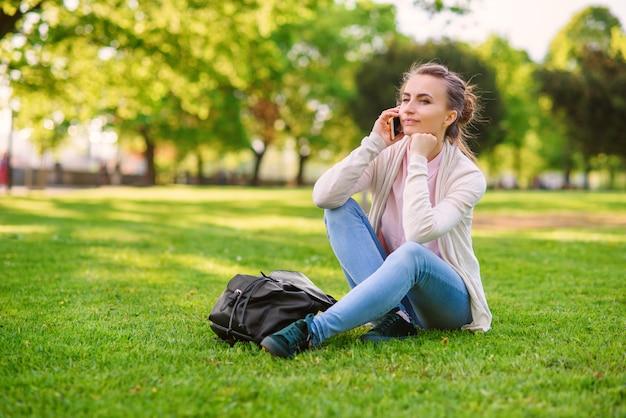 公園で屋外の快適な雰囲気の中で携帯電話でspaeking魅力的な女性