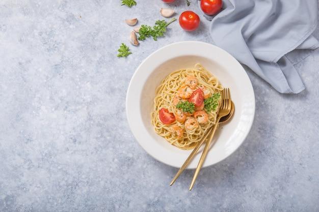 Spagetti marinara with shripms.  pasta dish on grey concrete  table
