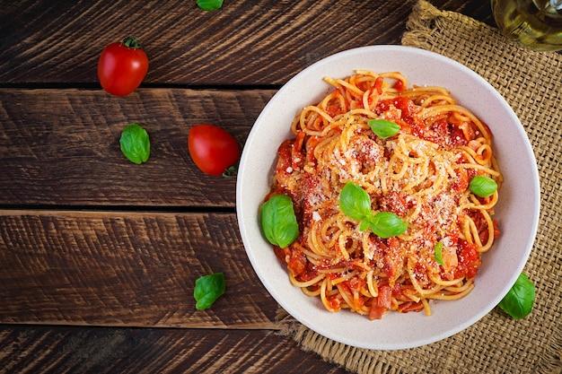 Спагетти alla amatriciana с гуанчиале, помидорами и сыром пекорино. итальянская здоровая еда. вид сверху, плоская планировка