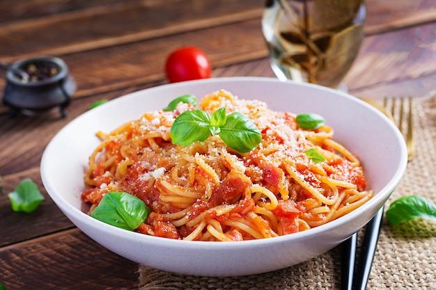 Спагетти alla amatriciana с гуанчиале, помидорами и сыром пекорино. итальянская здоровая еда.