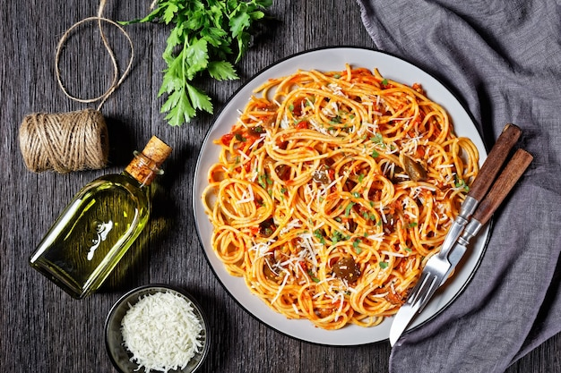 Spaghetti alla norma, classic pasta dish of sauteed eggplant tossed with tomato sauce and topped with shredded parmesan served on a plate, italian cuisine, horizontal view from above, flat lay