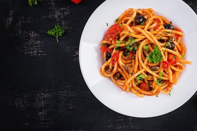 Spaghetti alla puttanesca - итальянское блюдо из пасты с помидорами, маслинами, каперсами, анчоусами и петрушкой. вид сверху, плоская планировка