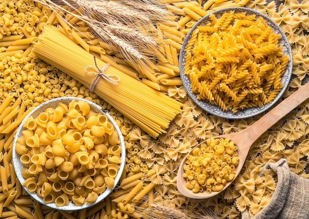 Спагетти и разные виды макарон в тарелке и на столе.