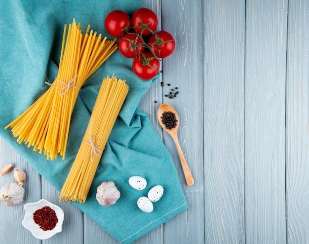 Спагетти и лингвини на синем фоне перец помидор чеснок яйца вид сверху копией пространства
