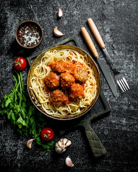 スパイス、ハーブ、トマトの入った鍋にスパゲッティとミートボール。素朴な背景に