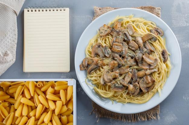 Спагетти и грибы с тетрадью, сырые макароны, кухонное полотенце в тарелке