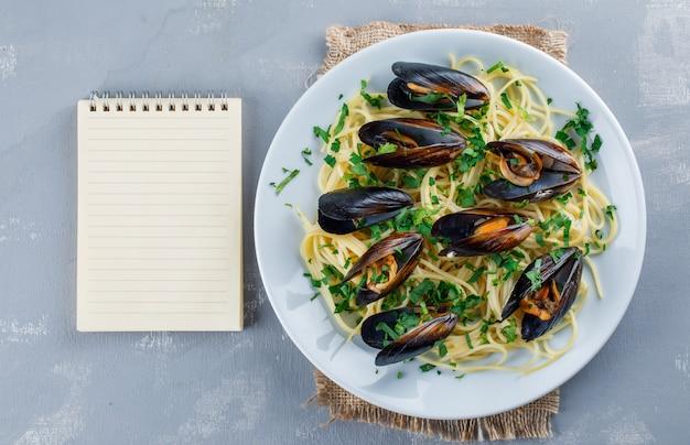 コピーブックとプレートのスパゲッティとムール貝