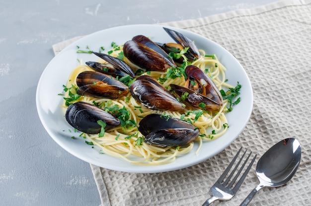 Спагетти и мидии с ложкой, вилкой в тарелке на гипсе и кухонным полотенцем