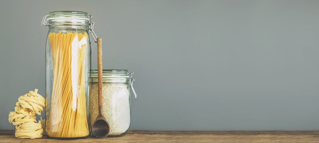 Спагетти и рис в банках на деревянном столе