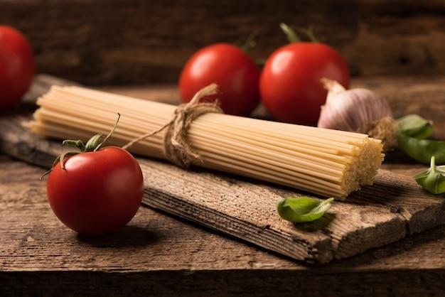 Спагетти и помидоры с зеленью на старом и винтажном деревянном столе