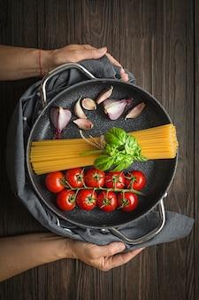 スパゲッティと木のパスタを調理するためのさまざまな食材