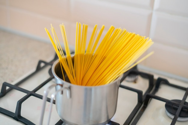 A spaghetti being cooked in the saucepan in boiling water on the stove in kitchen