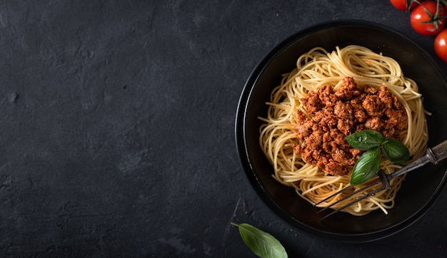 Spaghetti bolognese in a black bowl