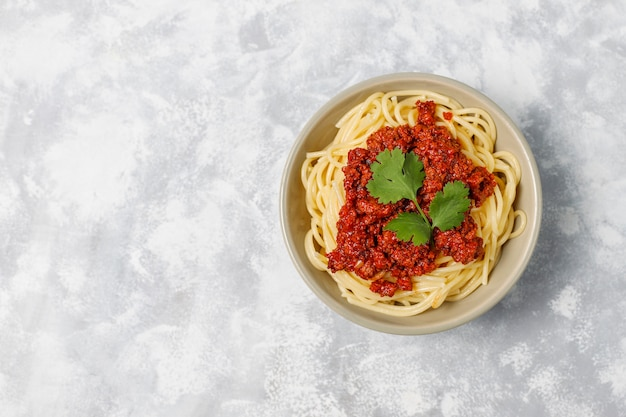 Spaghetti bolognese on grey concrete