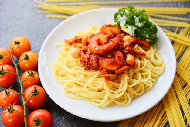 Spaghetti bolognese italian pasta with shrimp prawn served on white plate with tomato parsley in the restaurant italian food and menu