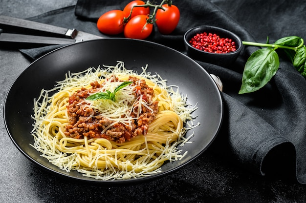 Spaghetti bolognese pasta with tomato and minced meat, parmesan cheese and basil. black background. top view