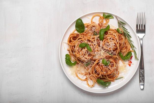 白いプレートにバジルとパルメザンチーズのスパゲッティボロネーゼ
