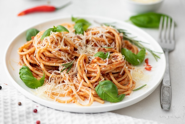 Spaghetti bolognese with basil and parmesan on a white plate