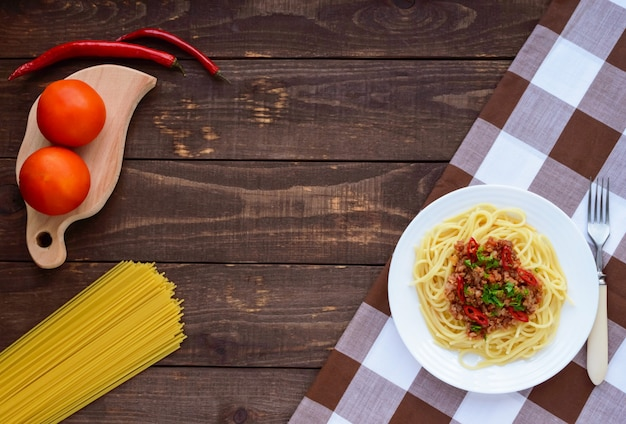 Spaghetti bolognese with chili on a white plate on a wooden table. the top view