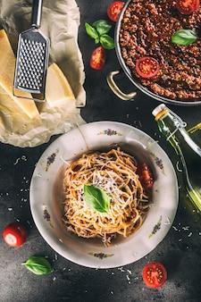 Спагетти болоньезе с ингредиентами, базиликом, помидорами, пармезаном и оливковым маслом.